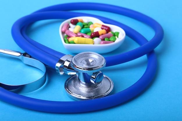 Estetoscopio, píldoras y cápsulas coloridas del surtido de la prescripción de rx en la placa.