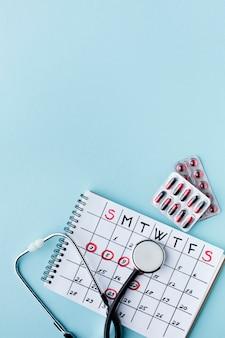 Estetoscopio y píldoras médicas para el tratamiento semanal.