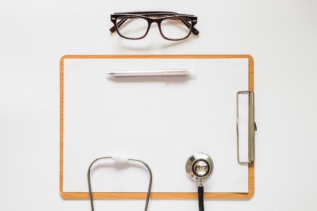 Estetoscopio; pluma y gafas en el portapapeles con papel sobre el fondo blanco