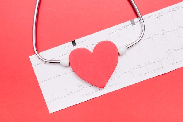 Estetoscopio de primer plano cerca del corazón y cardiograma