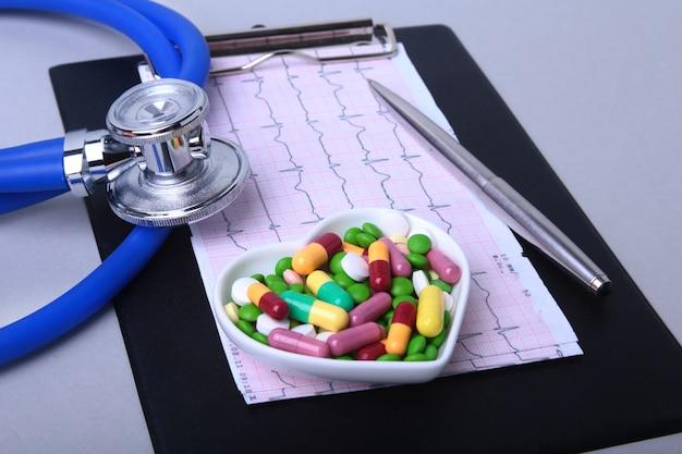Estetoscopio, receta rx y surtido colorido píldoras y cápsulas en placa.