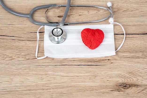 Estetoscopio y ritmo cardíaco rojo en el escritorio