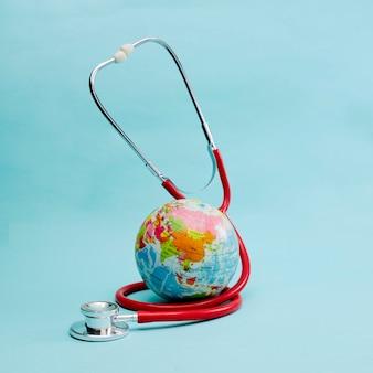 Estetoscopio rojo envuelto alrededor del globo en azul