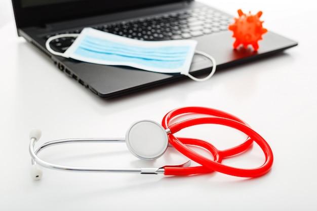Estetoscopio rojo, máscara protectora quirúrgica, modelo de coronavirus microscopio virus en la computadora portátil. prevención del coronavirus covid-19. concepto de salud de medicina.