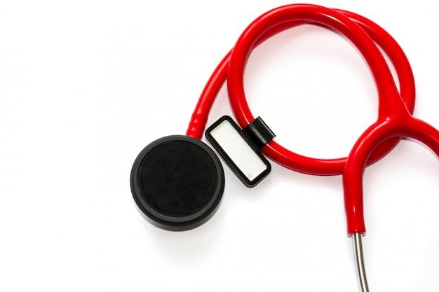 Estetoscopio rojo con la membrana negra y la etiqueta engomada blanca aisladas en el fondo blanco