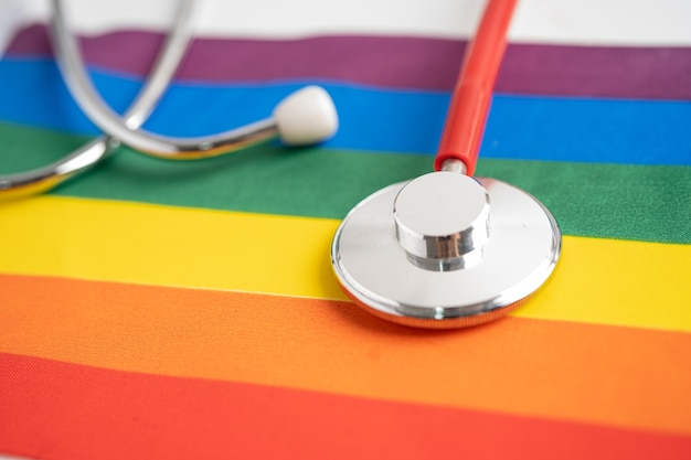 Estetoscopio rojo en el símbolo de fondo de la bandera del arco iris del mes del orgullo lgbt