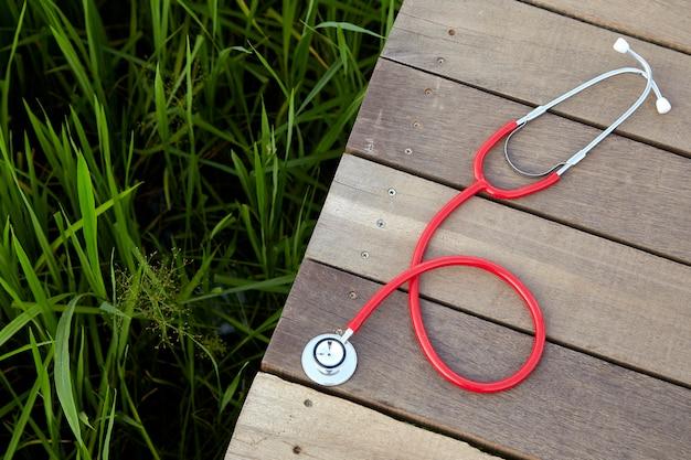Estetoscopio rojo sobre madera al aire libre