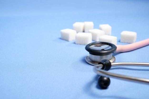 Estetoscopio rosa, terrones de azúcar en un espacio azul, diabetes. espacio para texto, enfoque selectivo.
