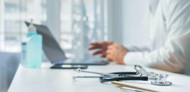 Estetoscopio y tablero de clip en el lugar de trabajo del médico en el fondo. el médico realiza una consulta al paciente en línea usando una computadora portátil.