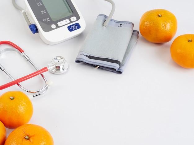 Estetoscopio y tensiómetro automático con naranjas