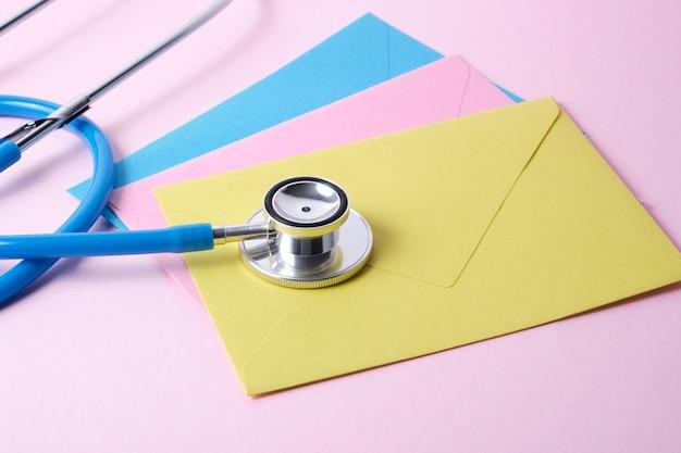 Estetoscopio y varios sobres de colores en el día del médico de superficie rosa