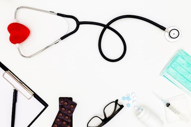 Estetoscopio, vista superior de la mesa de escritorio del médico, documento en blanco sobre fondo blanco, sobre las herramientas de trabajo del médico de la vista en blanco, concepto de escritorio de médico.