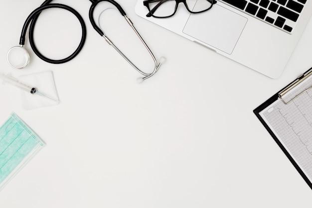 Estetoscopio, vista superior de la mesa del escritorio del médico, papel en blanco sobre fondo blanco, vista superior de las herramientas de trabajo del médico en blanco, estetoscopio, computadora portátil, anteojos y medicamentos sobre fondo blanco, médico