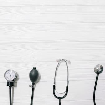 Estetoscopio y pulsímetro en mesa de madera