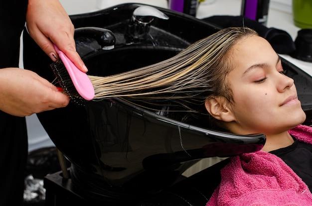 Estilista aplicando mascarilla y peinando a los clientes el cabello mojado con un cepillo en un lavabo negro.