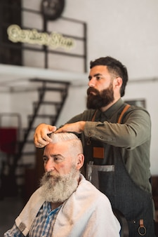 Estilista de cabello corrigiendo peinado a cliente hombre.