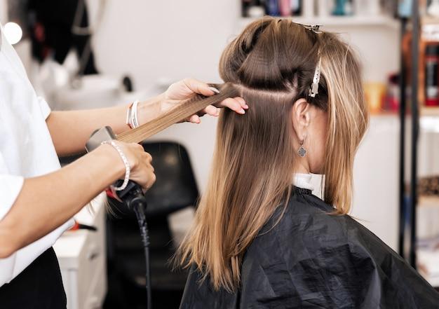 El estilista crea volumen y estilo para el cabello castaño en la cabeza de una mujer