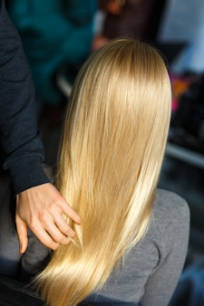 Estilista demostrar cabello rubio femenino