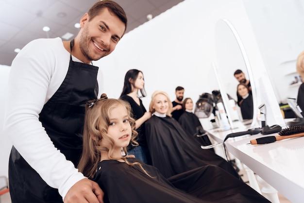 El estilista femenino hace el corte de pelo de la niña con el pelo rizado.