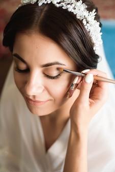 Estilista hace maquillaje novia en el día de la boda