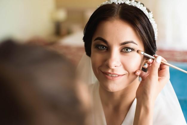 El estilista hace maquillaje a la novia en el día de la boda.