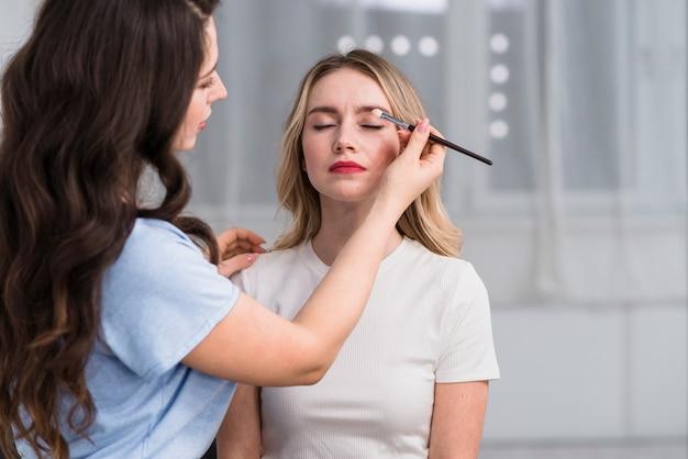Estilista haciendo maquillaje de sombra de ojos a mujer rubia.