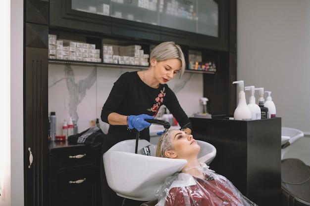 Estilista lavando el cabello del cliente en el salón