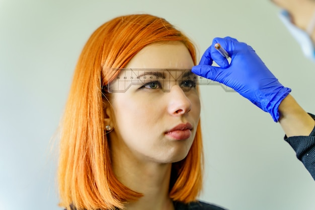 Estilista midiendo las cejas con la regla sobre una mujer pelirroja. flujo de trabajo de micropigmentación en un salón de belleza.