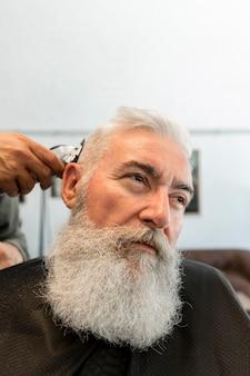Estilista del pelo que corta el pelo al hombre mayor en peluquería