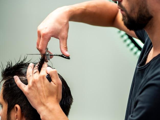 Estilista que corta el cabello del cliente ayudado por tijeras