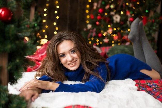 Estilo de cabello largo y saludable. dama sobre luces de árbol de navidad