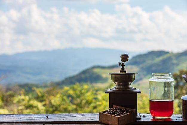 Estilo clásico de los molinillos de café antiguos en el estante y la montaña con la naturaleza del cielo de la nube