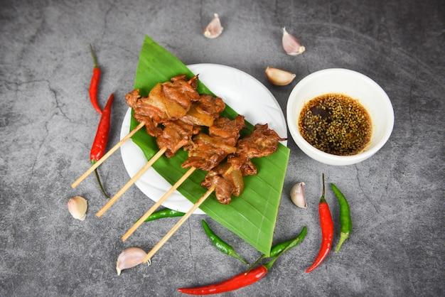 Estilo de comida callejera asiática tailandesa de cerdo a la parrilla, rebanada de palitos de brocheta de cerdo a la parrilla sobre hoja de plátano en un plato blanco con salsa de ajo y chile