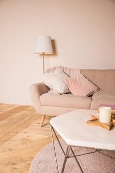 Estilo loft. elegante interior con mesa pequeña con velas. mesa con elegantes accesorios y sofá con almohadas.