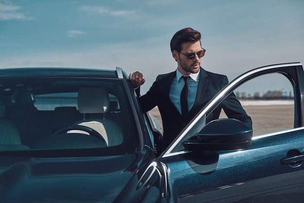 Estilo de lujo. apuesto joven empresario entrando en su coche mientras está de pie al aire libre