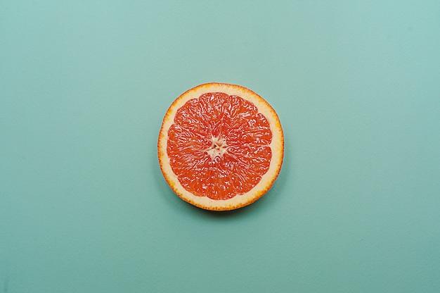 Estilo minimalista, diseño creativo, naranja y pomelo sobre fondo turquesa.