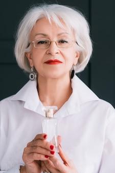 Estilo de moda de mujer mayor. tendencias de perfumería. botella de fragancia cara en manos femeninas.