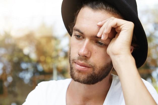 Estilo y moda. retrato de joven guapo modelo masculino barbudo con cabello rubio posando en sombrero negro y camiseta blanca