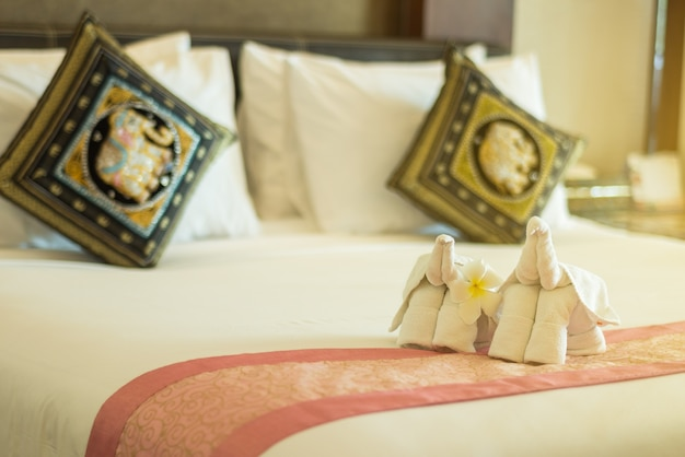 Estilo moderno de dormitorio con toalla doblada en forma de elefante en la cama