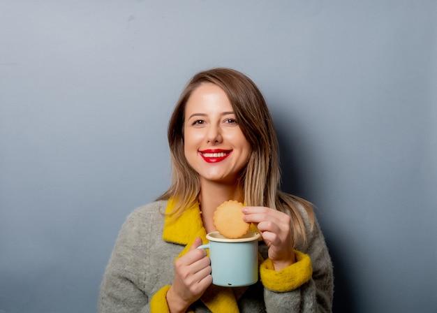 Estilo mujer en abrigo con taza de café y galletas