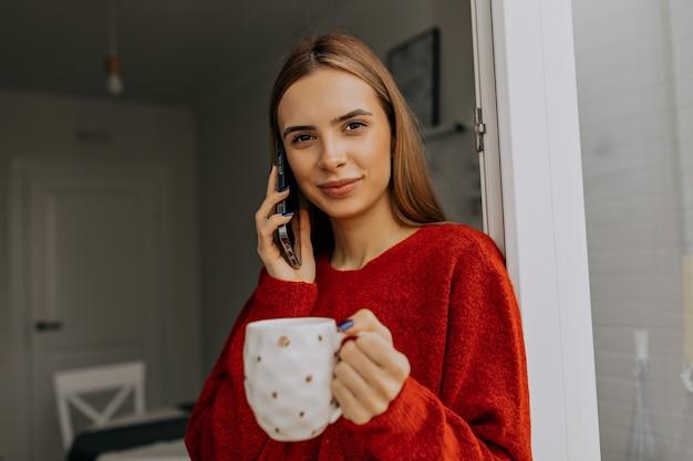 Estilo de mujer espectacular con cabello castaño claro vistiendo jersey rojo con teléfono inteligente y tomando café en casa por la mañana