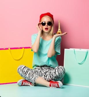 Estilo mujer en gafas de sol con bolsas de compras y pequeña torre eiffel en pared rosa