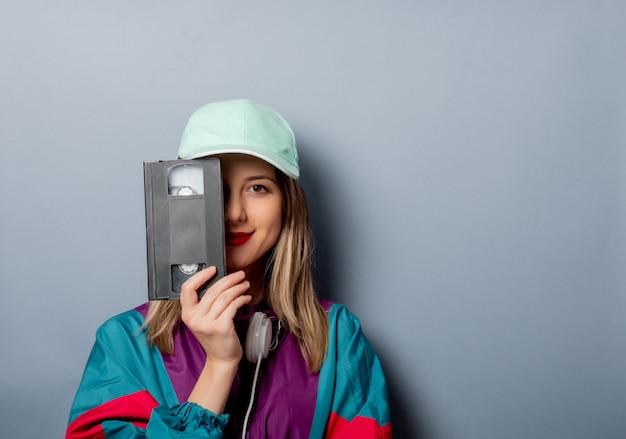 Estilo mujer en ropa de los años 90 con videocasete vhs