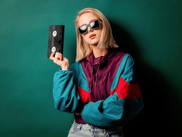 Estilo mujer en ropa punk de los 90 con cassette vhs