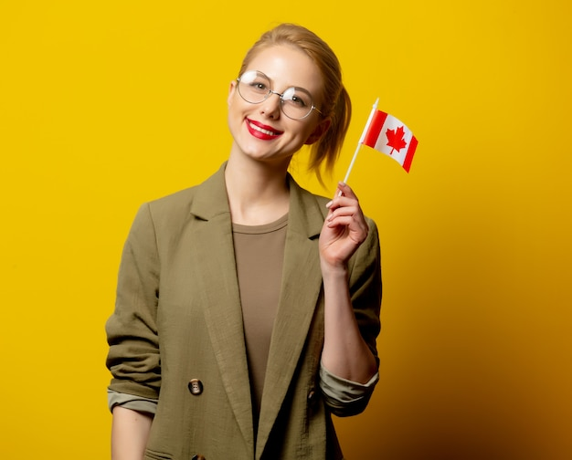 Estilo mujer rubia en chaqueta con bandera canadiense en amarillo