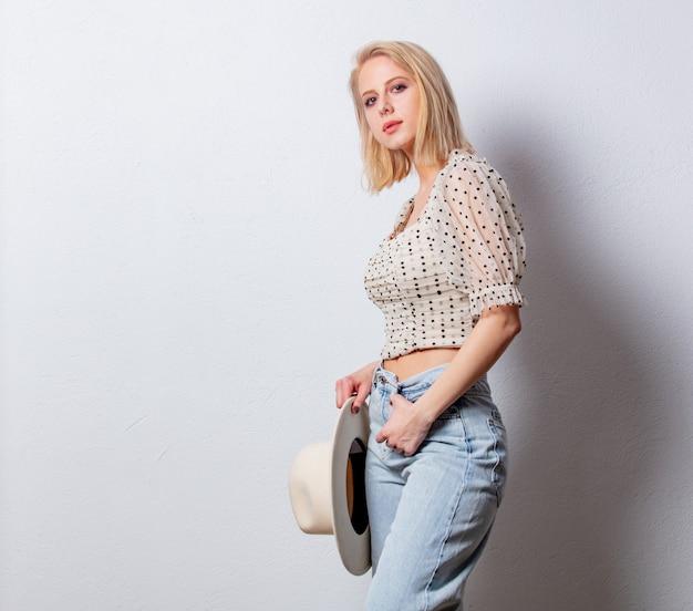 Estilo mujer rubia en jeans y blusa de lunares