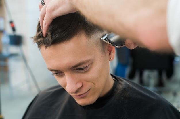 Estilo profesional cerrar vista lateral del joven corte de pelo por peluquero con maquinilla de afeitar eléctrica en la barbería