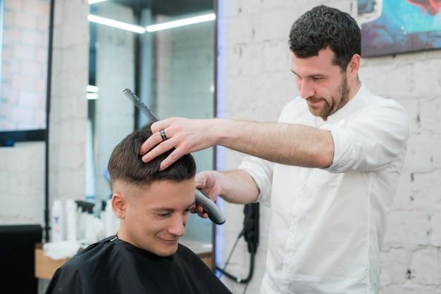 Estilo profesional cerrar vista lateral del joven satisfecho corte de pelo por peluquería con maquinilla de afeitar eléctrica en la barbería