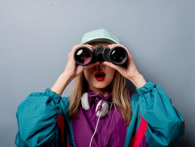 Estilo de ropa de mujer en los años 90 con binoculares
