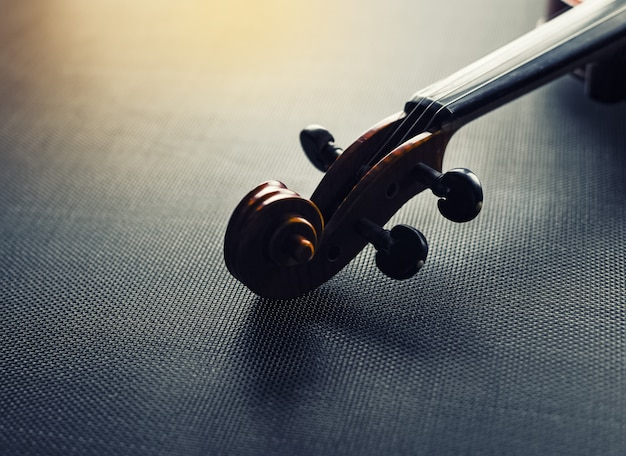 El estilo de silueta de scroll of violin, poner sobre fondo de lienzo negro, luz borrosa alrededor, tono vintage y artístico.